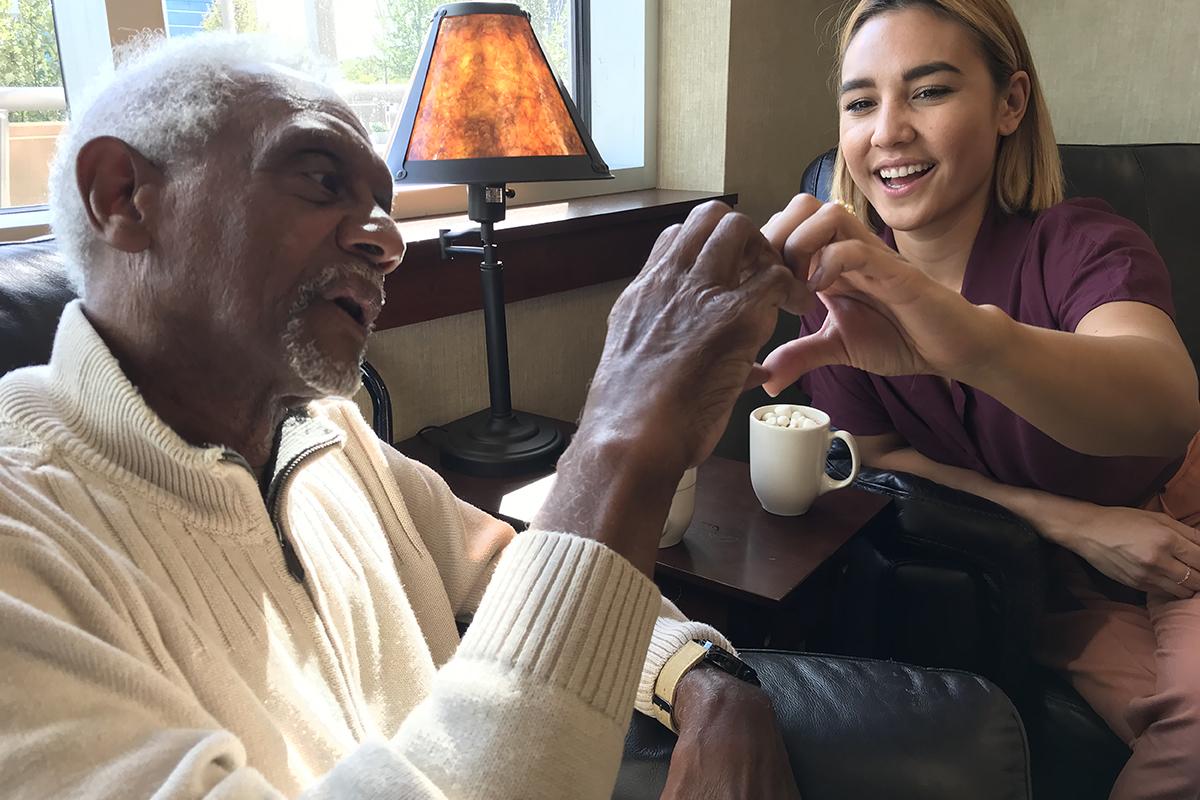 Older man and caregiver smiling