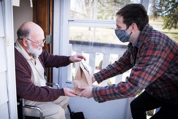 Gentleman delivering sack lunch to older man