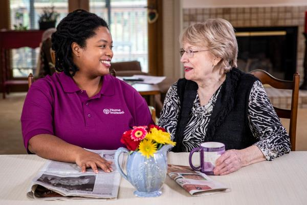 Caregiver and senior woman smiling over coffee