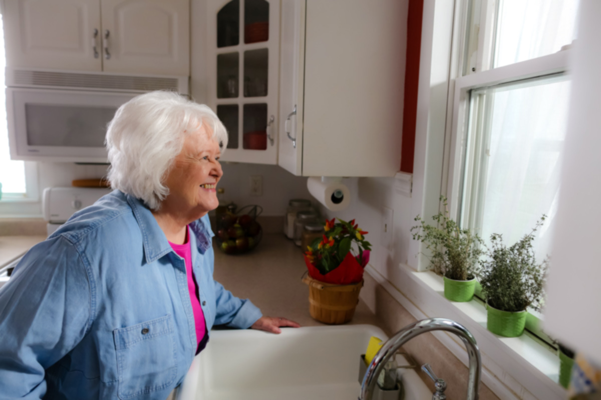 Caregiver smiles and looks out kitchen window at home