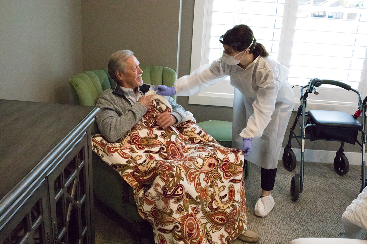 Caregiver wearing PPE helping senior