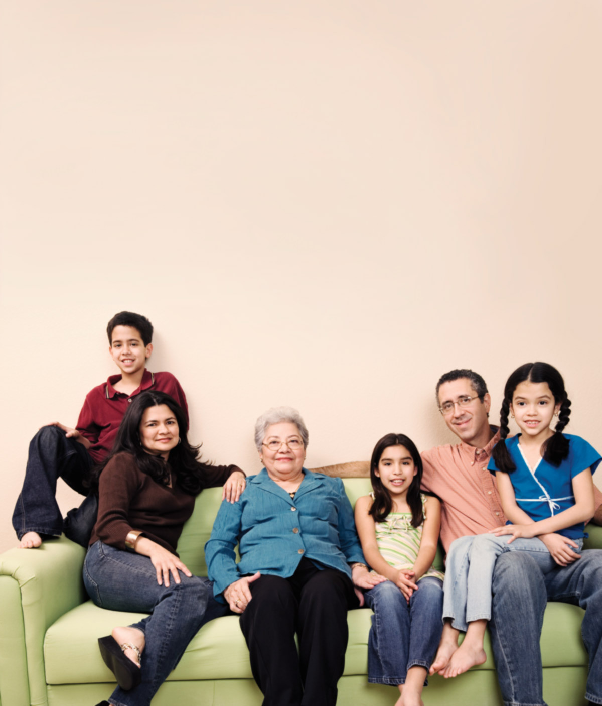 Senior woman sits on couch smiling with family surrounding her