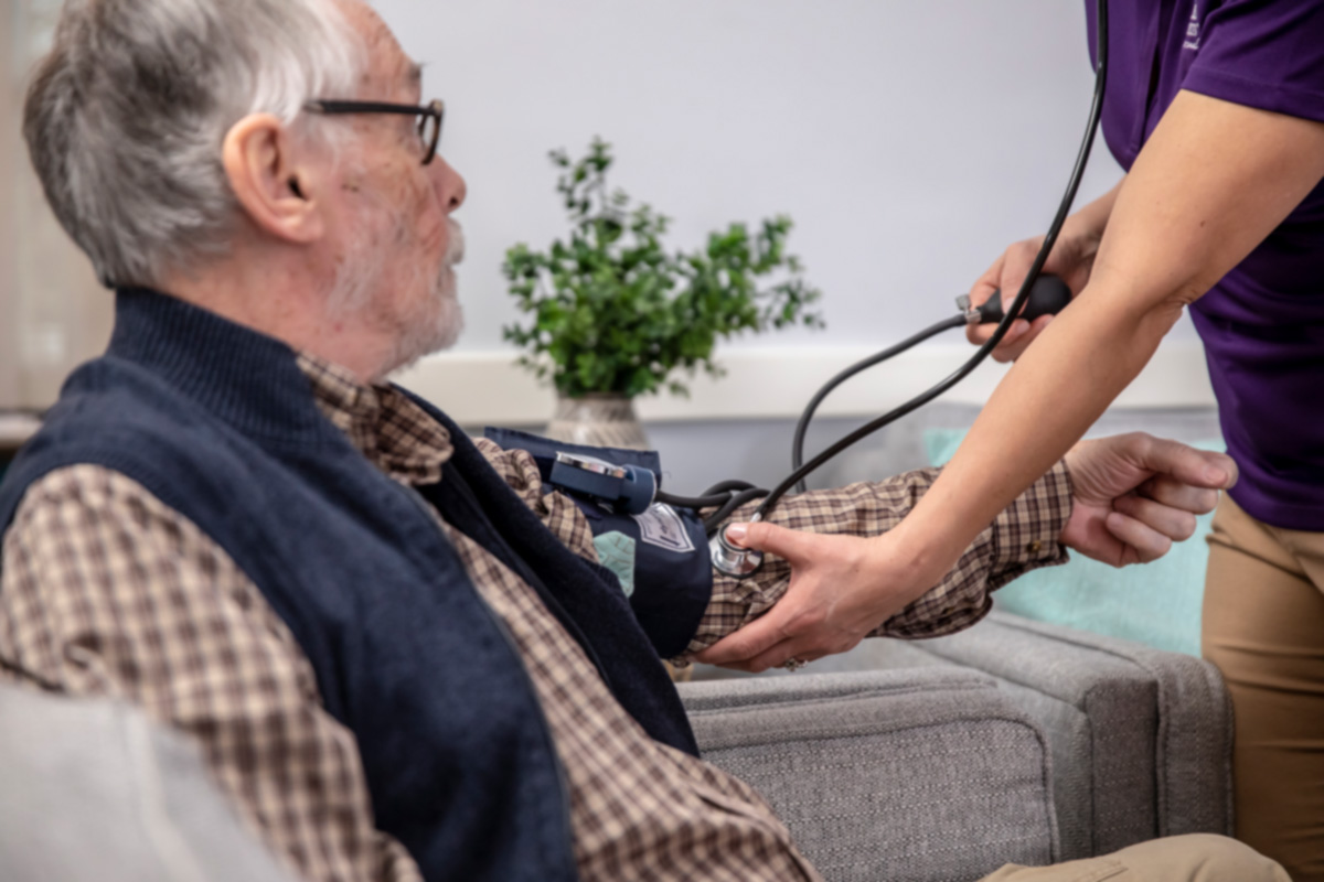 Home Instead Caregiver taking blood pressure reading for senior man at home
