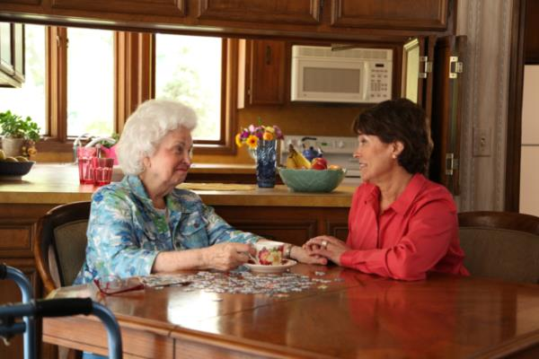 Senior woman and daughter sit talking at the kitchen table at home