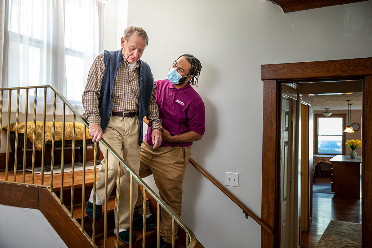 Home Instead Caregiver wearing mask helps senior man walking down stairs at home