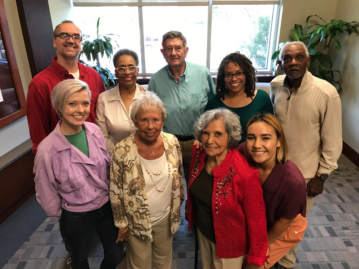 Group of seniors and family caregivers smile and pose