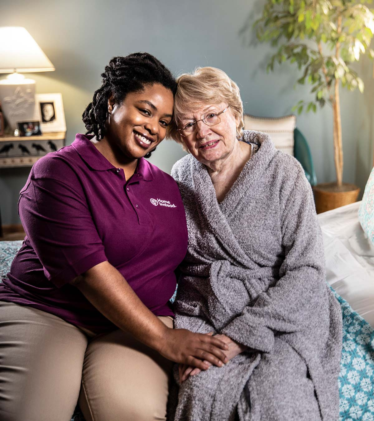 Home Instead CAREGiver and senior sitting on bed smiling