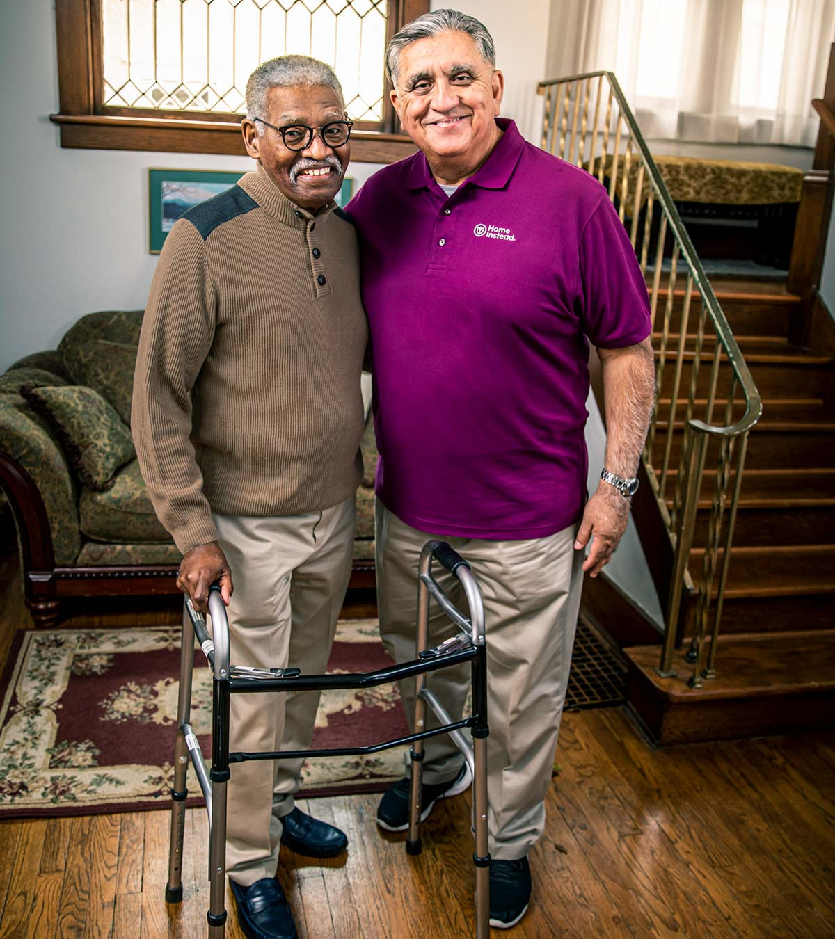 Home Instead CAREGiver and senior smiling while standing in home
