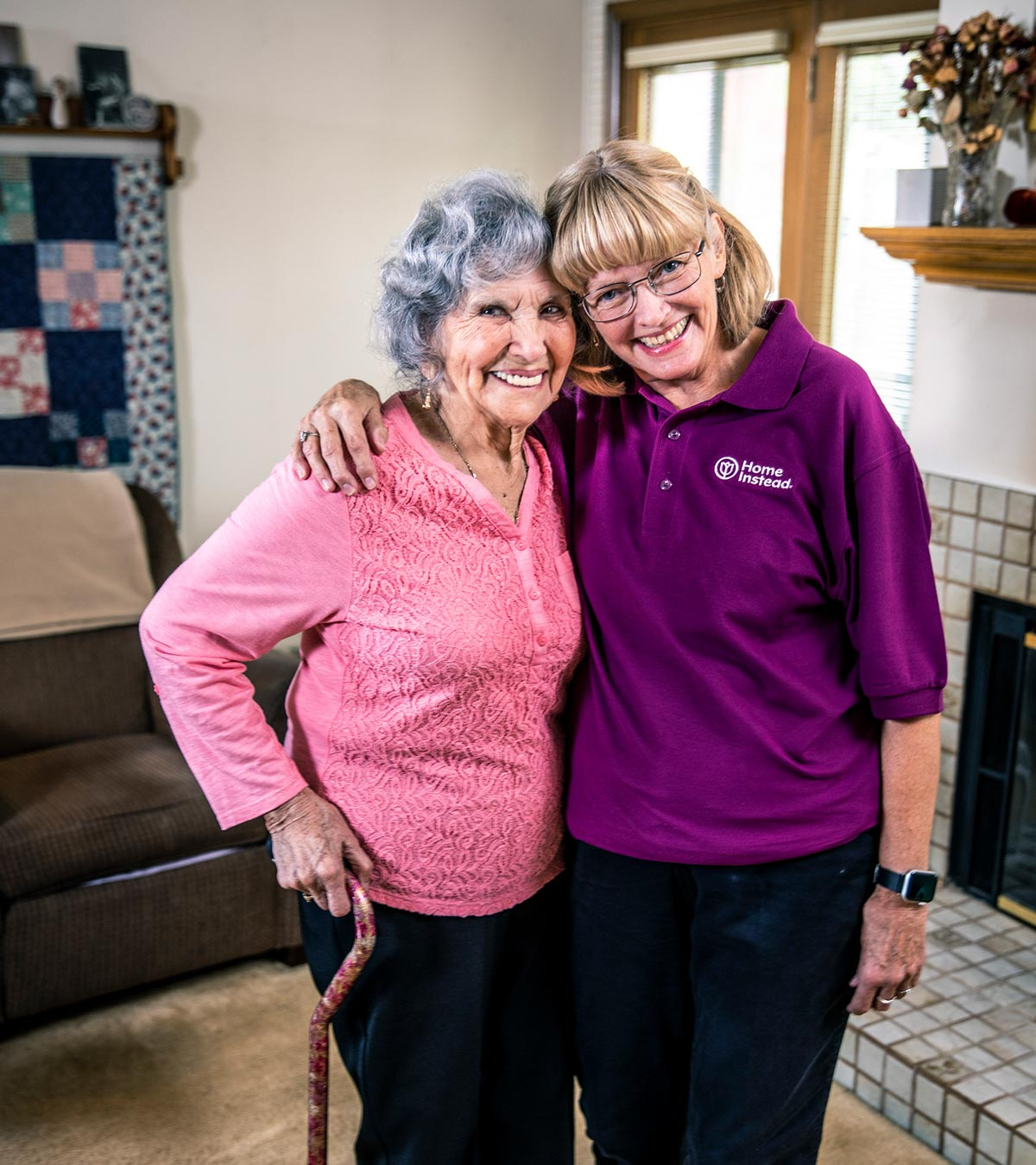 Home Instead CAREGiver and senior standing together smiling in home