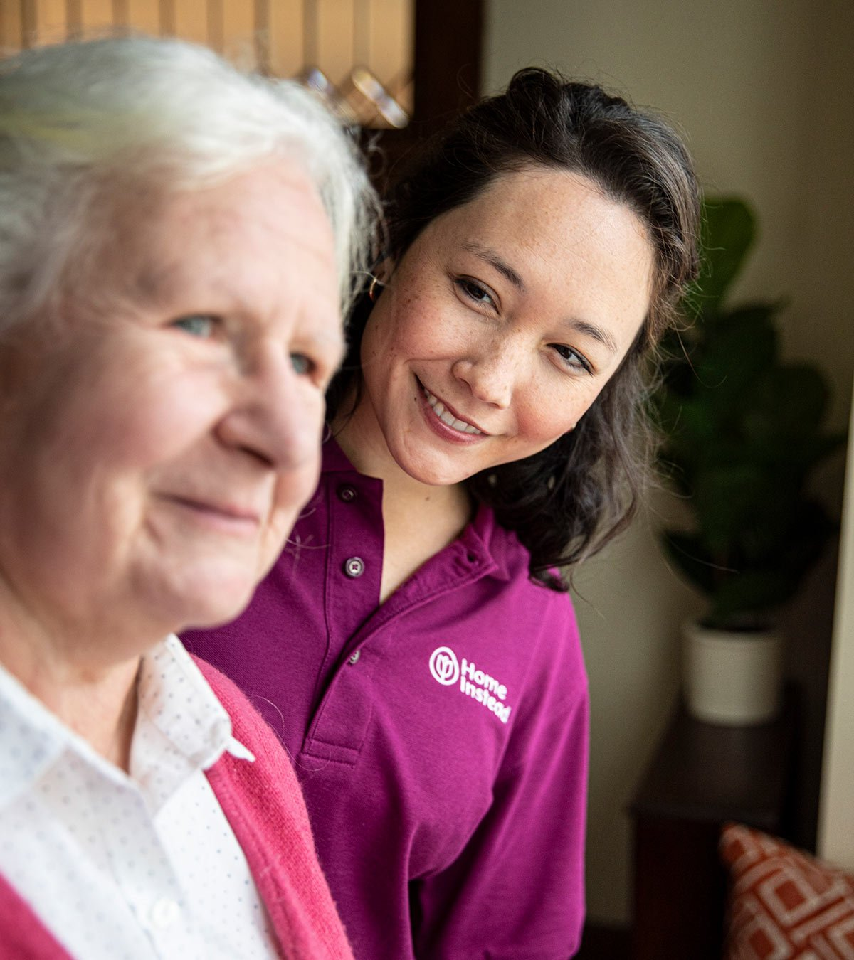 Home Instead CAREGiver smiling and looking at senior performing elder care