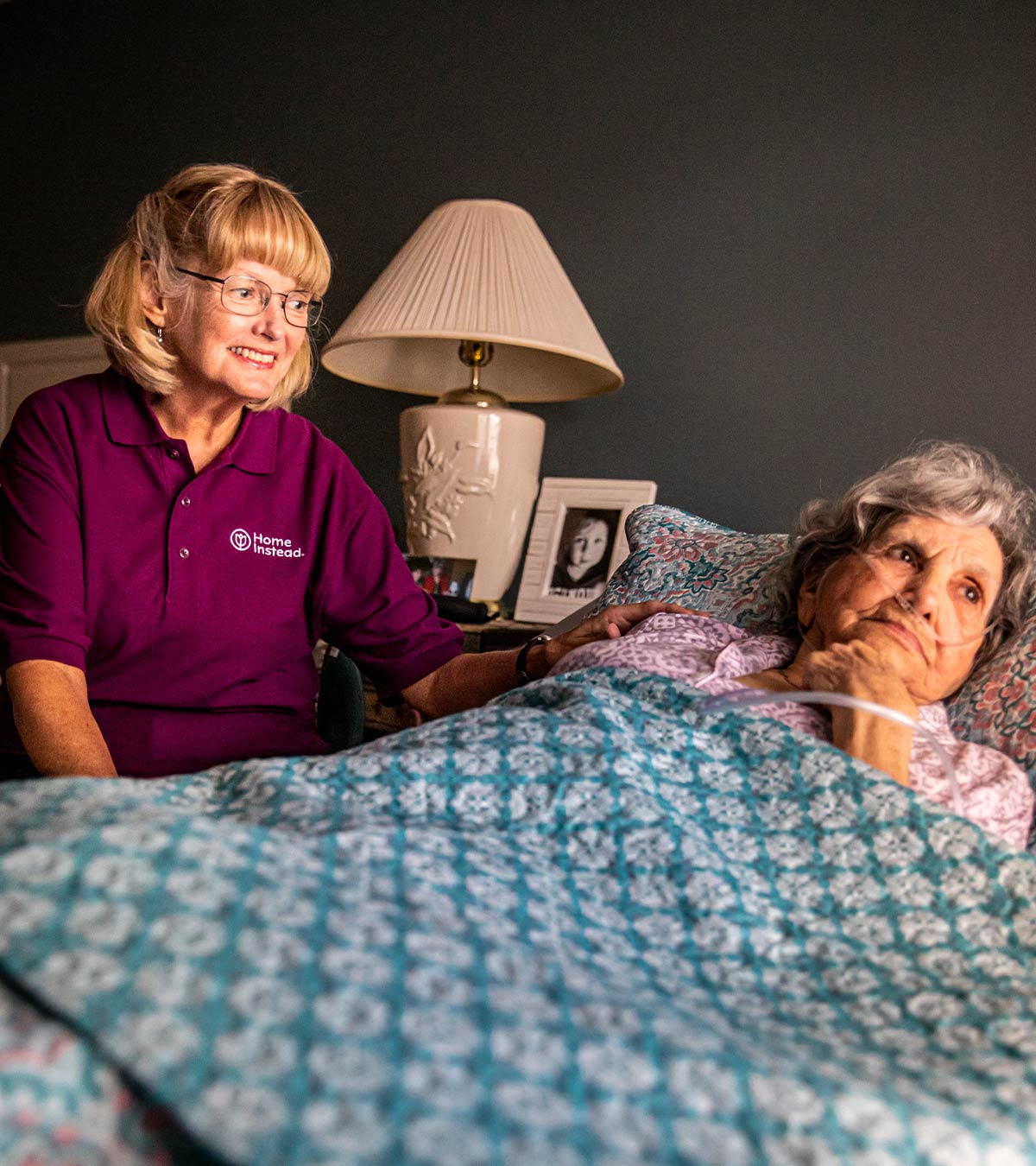 Home Instead CAREGiver sitting next to bed with senior
